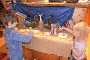 Children moving the figures in a Nativity Scene as they anticipate Christmas