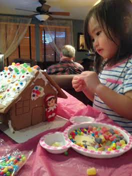 Anna decorating a gingerbread house