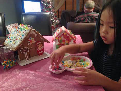 Grace adding candy decorations to gingerbread houses