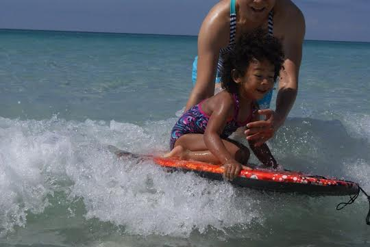 Surf's Up! Beth helps Gabby catch a wave on the boogie board...