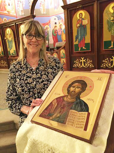 My friend took this picture of me with one of the two icons I wrote for the stands in front of the solea at St. John Orthodox Church. The worn spot is where worshipers have kissed the icon. I never learned to seal egg tempera very well.