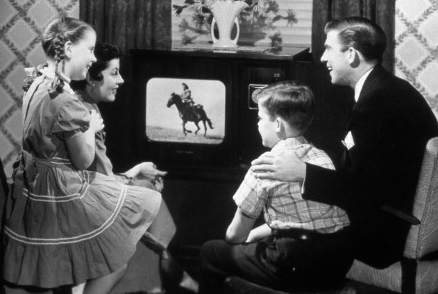 1950s family of four watching black and white television program of a cowboy riding a horse